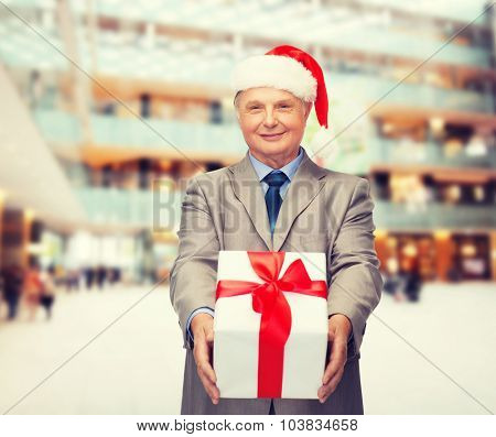 business, christmas, presents and people concept - smiling senior man in suit and santa helper hat with gift over shopping center background