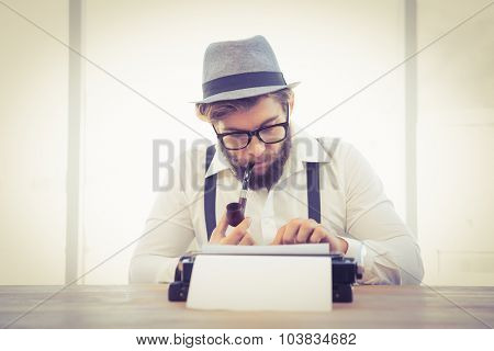Hipster smoking pipe while working on typewriter at desk in office