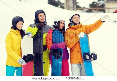 winter, leisure, extreme sport, friendship and people concept - happy friends in helmets with snowboards