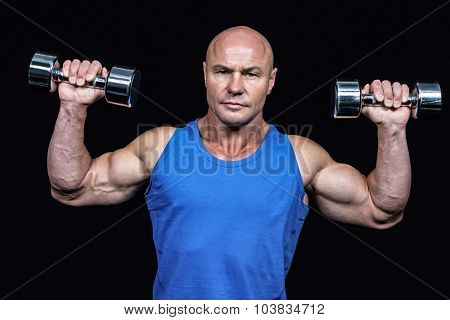 Portrait of man lifting dumbbells with arms raised against black background