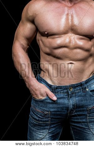 Midsection of shirtless man with hands in pocket against black background