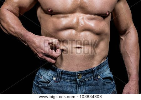 Midsection of muscular man holding skin against black background