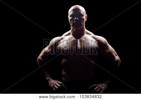 Portrait of muscular man with hands on hip against black background