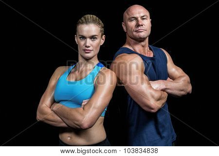 Portrait of confident strong man and woman standing against black background