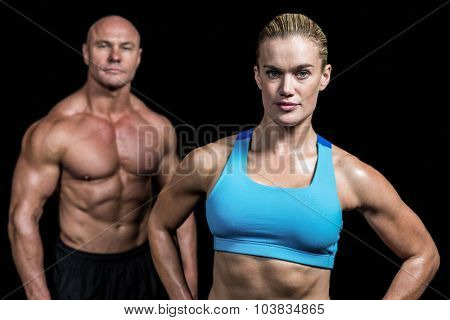 Portrait of fit trainers standing against black background