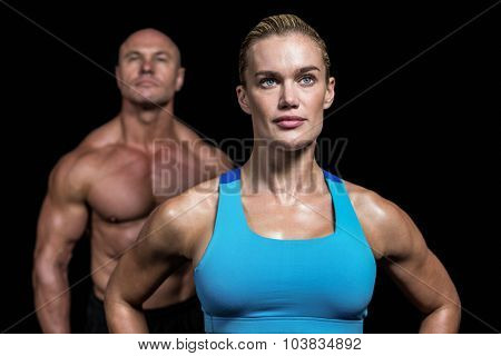 Muscular trainers looking away against black background