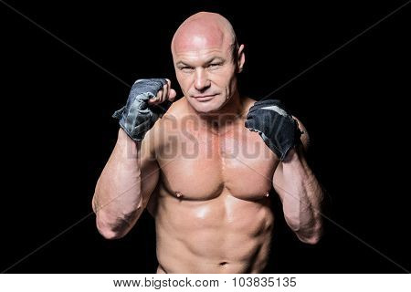 Portrait of fighter with gloves against black background