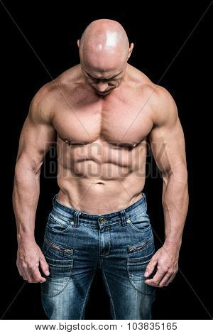 Muscular sad man looking down while standing against black background