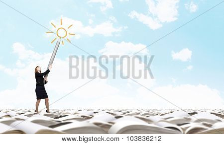Young businesswoman pointing up with big pencil