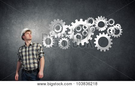 Young man builder looking at gears mechanism
