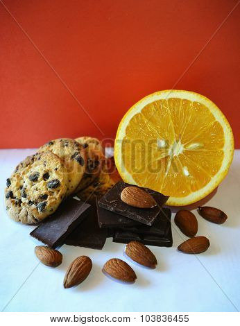 Orange, dark chocolate, almonds and cookies with chocolate chips on red background in vintage colors