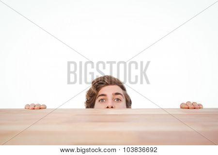 Portrait of man hiding behind desk against white background