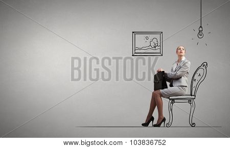 Young pretty businesswoman sitting on chair with briefcase in hands