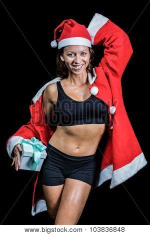 Portrait of happy athlete with hand behind head holding Christmas gift against black background