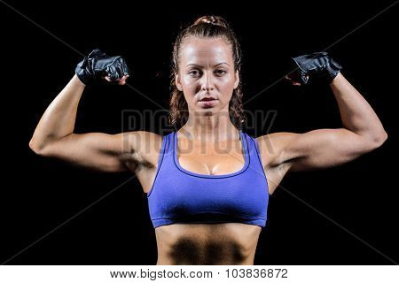 Portrait of woman with gloves flexing muscles against black background