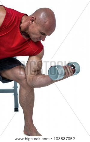 Bald man exercising by lifting dumbbells against white background