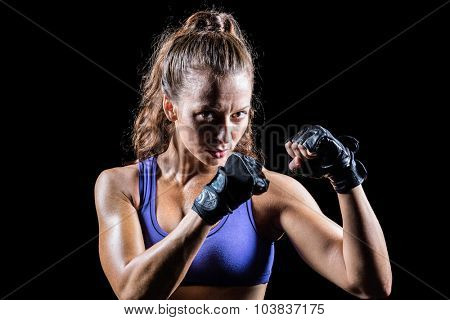 Portrait of female confident boxer with fighting stance against black background