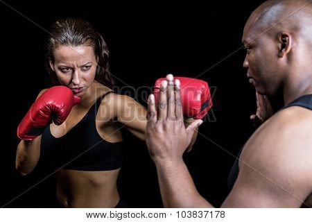 Female boxer practicing with trainer against black background