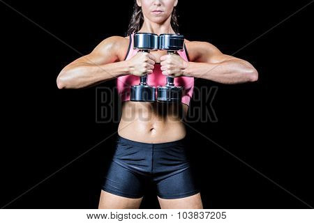 Midsection of slim woman exercising with dumbbells against black background