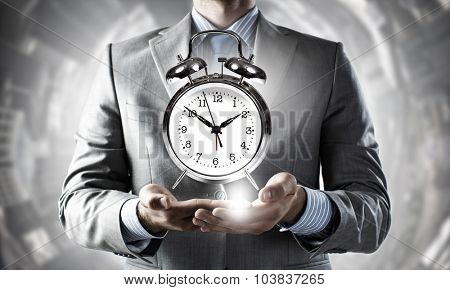 Close up of man holding alarm clock in hands