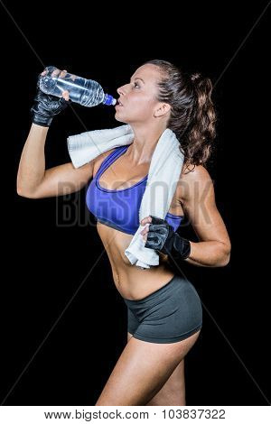 Fit woman drinking water against black background