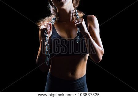 Midsection of female athlete with chain against black background
