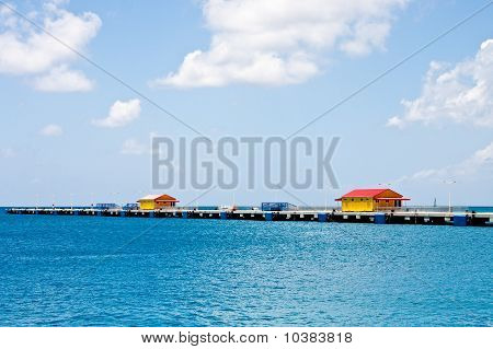 Yellow And Red Buildings On Pier On Brilliant Blue Water