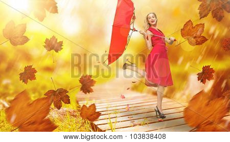 Elegant blonde holding umbrella against wooden trail across countryside