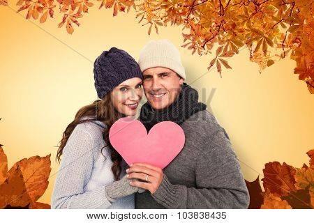 Happy couple in warm clothing holding heart against autumn leaves pattern
