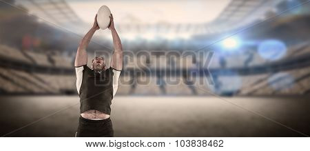 Rugby player catching the ball against rugby stadium