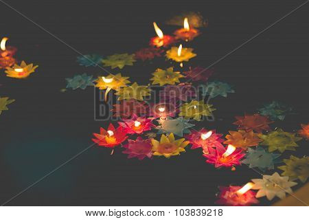 Flower-shaped Candle Burning In The Pool Of Spirit At Chinese Temple