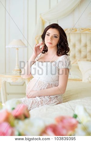 Brunette Pregnant Young Woman Sits In A Beautiful Interior With Roses