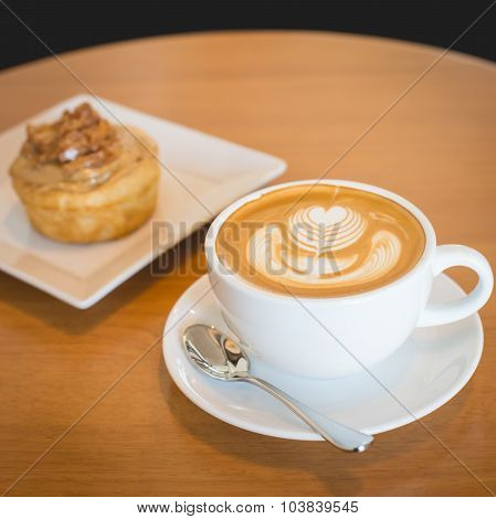 Apple Cinnamon Roll Served With Latte Coffee On The Table At Restaurant