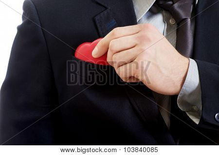 Handsome businessman putting small heart from pocket.
