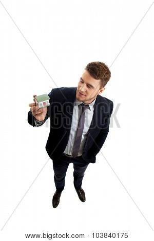 Businessman holding small house model.