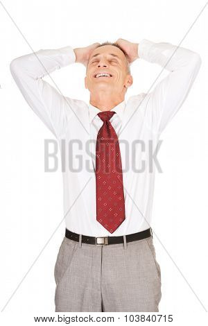 Relaxing businessman holding arms on head.