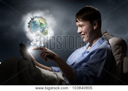 Young teenager guy in bed using tablet pc. Elements of this image are furnished by NASA