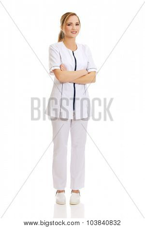 Young female doctor or nurse with folded arms.