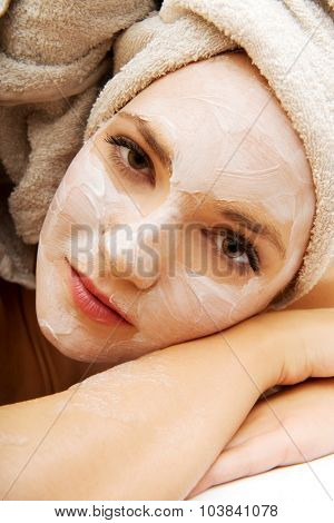 Young spa woman relaxing in bathroom with cream moisturizer.