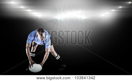 Rugby player holding ball while playing against spotlight