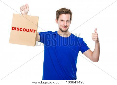 Man with shopping bag and thumb up and showing a word discount