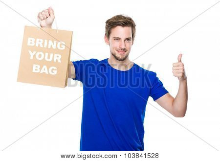 Man with shopping bag and thumb up and showing phrase bring your bag