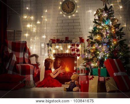 girl warms his hands by the fireplace