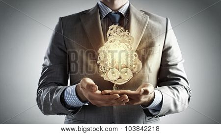 Close up of businessman in suit holding metal gears in hands