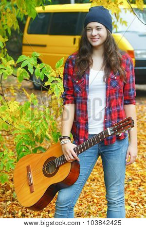 Portrait Of Classic Guitar Girl Player Standing At Yellow Van And Autumn Yellow Tree Background