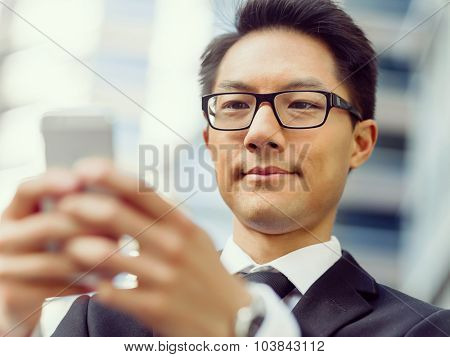 Businessman in city holding his mobile