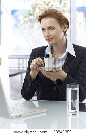 Young businesswoman sitting at desk, drinking coffee, having laptop computer.