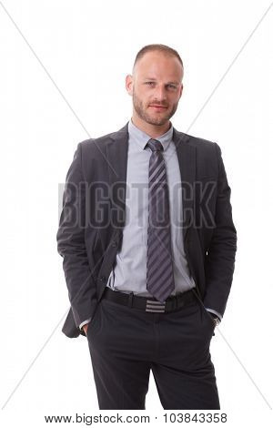 Confident businessman standing hands in pockets, looking at camera.