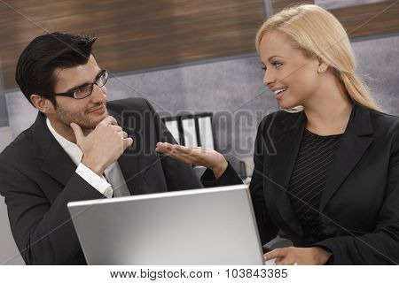 Young businesspeople working together, using laptop computer, talking, smiling.