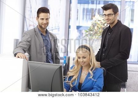 Young businesspeople working together in bright office, using computer.